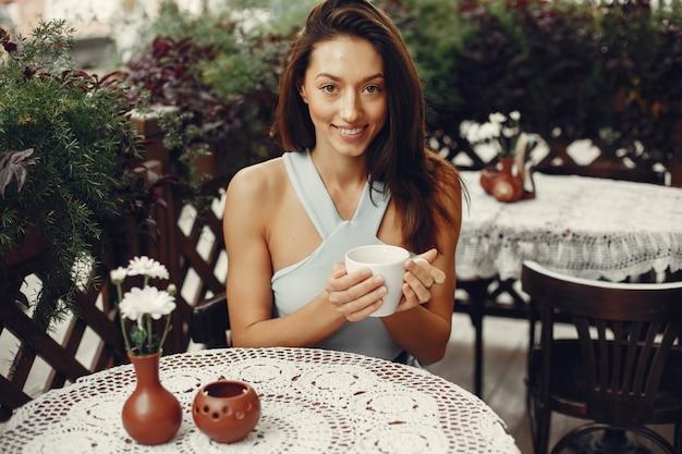 Fille de mode buvant un café dans un café Photo gratuit
