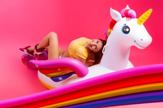 Fille à La Mode De L'été, Humeur Rose Et Joyeuse. Belle Femme Mince Dans Un Vêtement D'été, S'amuser Et Profiter De La Vie Sur Une Licorne Gonflable Blanche Photo Premium