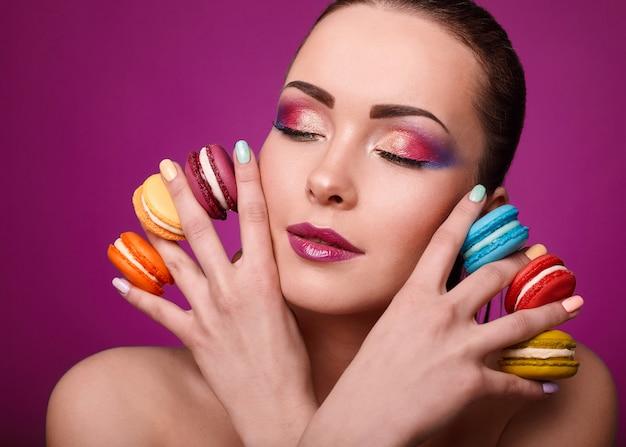 Fille de modèle de mode beauté glamour avec maquillage coloré et macarons. Photo Premium