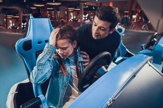 Une fille monte dans une voiture bleue en arcade une fille perd Photo Premium
