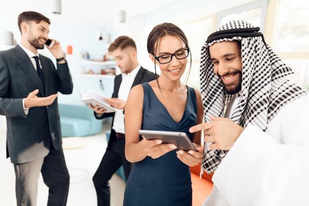 Fille montre quelque chose à un homme portant des vêtements arabes sur une tablette. Photo Premium