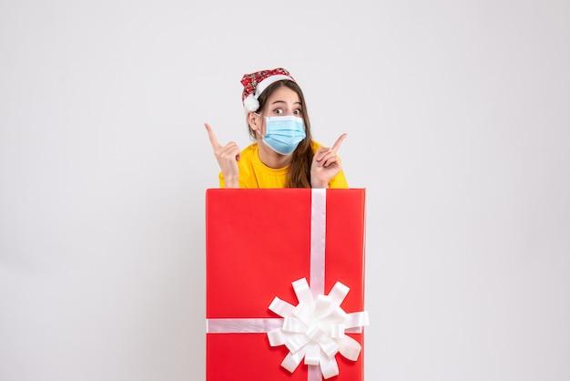 Fille De Noël Aux Yeux écarquillés Avec Bonnet De Noel Pointant Sur Quelque Chose Debout Derrière Un Grand Cadeau De Noël Sur Blanc Photo gratuit