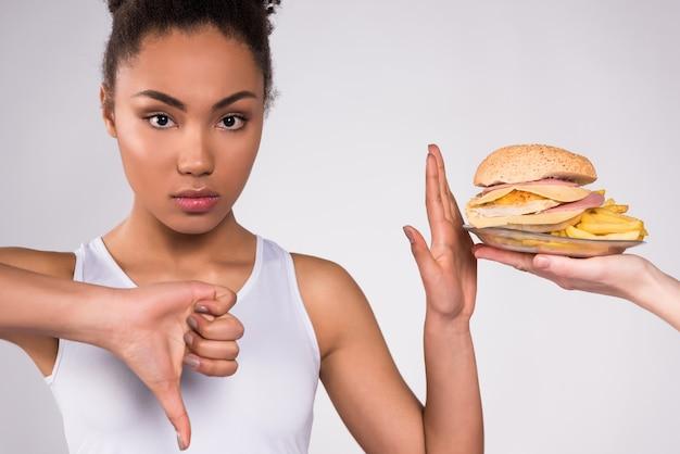 La fille noire a mis son doigt dedans montre que la nourriture nuisible. Photo Premium