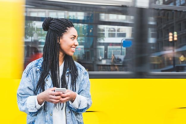 Fille noire en tapant sur un smartphone à berlin Photo Premium