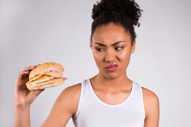 Fille noire tenant cheeseburger isolé. Photo Premium