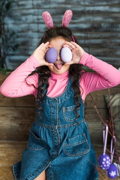 Fille avec des oeufs de pâques montrant la langue Photo gratuit