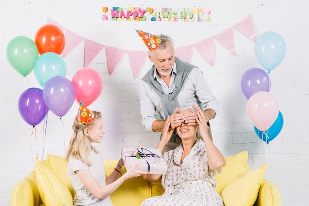Fille offrant un cadeau surprise à sa grand-mère pendant que son mari couvre les yeux Photo gratuit