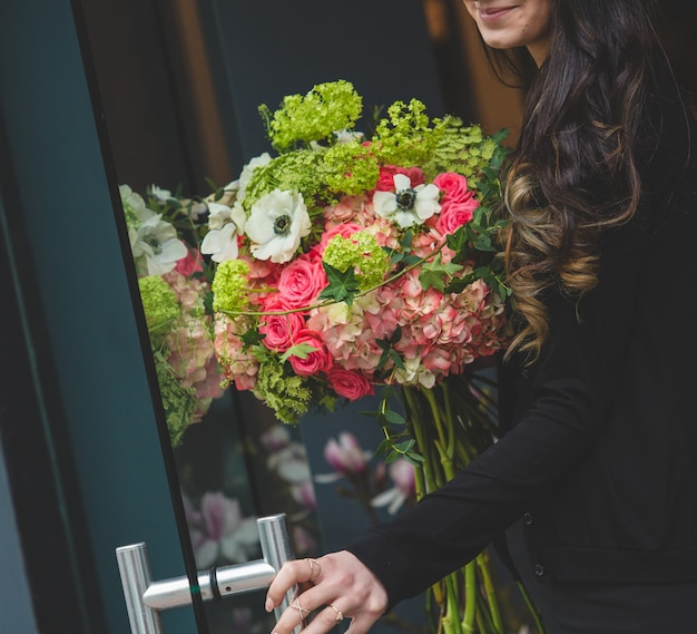 Fille ouvrant la porte avec un bouquet de plusieurs types de fleurs dans une autre main Photo gratuit