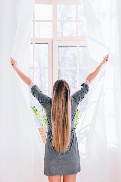 Fille ouvrant des rideaux Photo gratuit