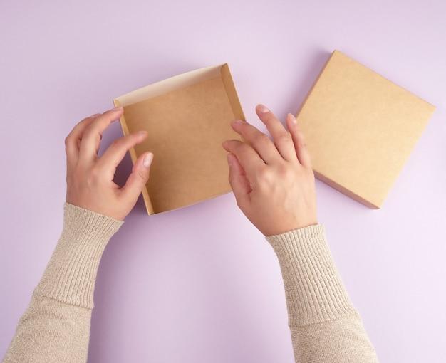 Fille ouvre une boîte carrée brune sur un fond violet Photo Premium