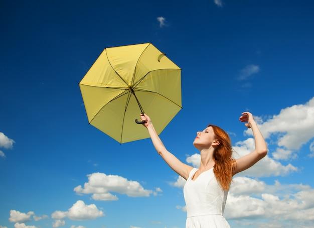 Fille avec parapluie au fond du ciel. Photo Premium