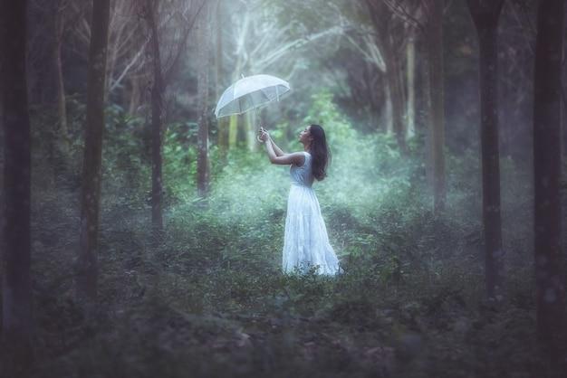 Une fille avec un parapluie blanc se trouve dans la forêt. Photo Premium