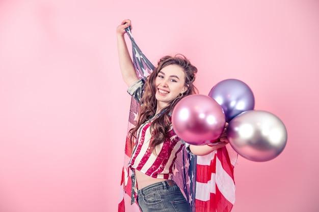 Fille Patriotique Avec Le Drapeau De L'amérique Sur Un Fond Coloré Photo gratuit