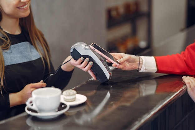 Fille Payant Son Café Au Lait Avec Un Smartphone Par La Technologie Sans Contact Pay Pass Photo gratuit