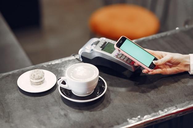 Fille Payant Son Café Au Lait Avec Un Smartphone Par La Technologie Sans Contact Pay Pass Photo gratuit