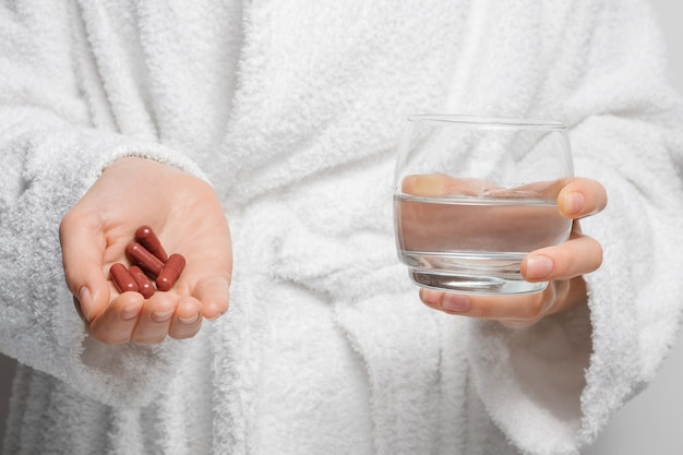 Une Fille En Peignoir Se Prépare à Prendre Des Pilules Avec Des Médicaments, Des Capsules Et Un Verre D'eau Dans Ses Mains. Photo Premium