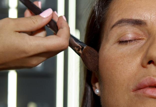 La Fille Peint De La Poudre Sur Le Visage, Complète Le Maquillage Des Yeux Enfumés Dans Le Salon De Beauté. Soin Professionnel De La Peau. Photo Premium