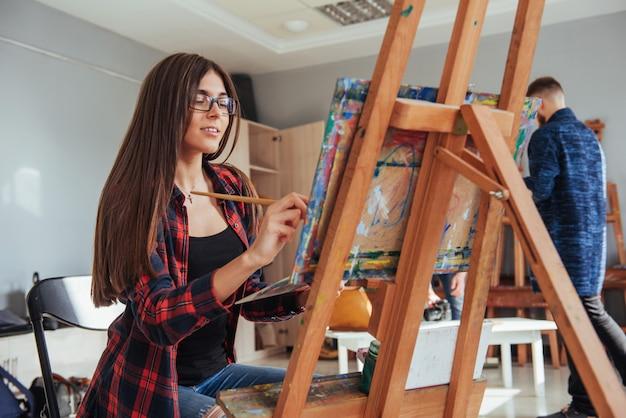 Fille peintre pensif créatif peint une image colorée sur toile avec des couleurs à l'huile en atelier. Photo Premium