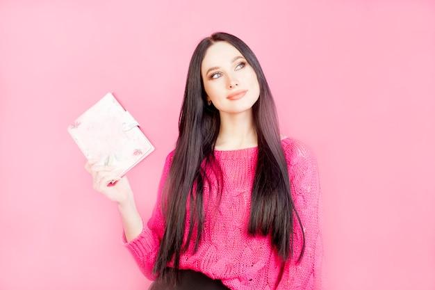 Fille Pensive Avec Un Bloc-notes, Sur Fond Rose. Le Concept De Femme D'affaires Ou De Planification Des Affaires Féminines, La Vie D'une Fille. Photo Premium