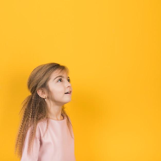 Fille pensive, levant sur fond jaune Photo gratuit