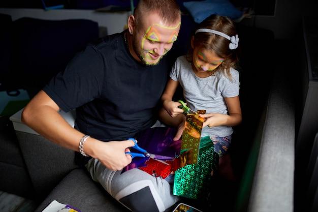 Fille Et Père S'amusant à Faire De L'artisanat Ensemble à La Maison Sur Le Canapé, Coupant Un Papier Avec Des Ciseaux, Lumière Noire, Fête Des Pères, Famille. Photo Premium