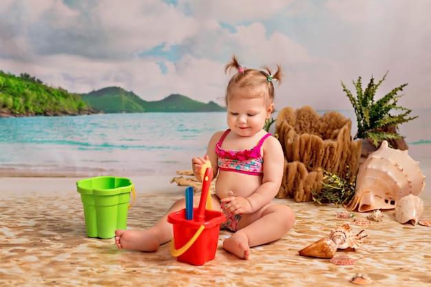 Fille Sur Une Plage De Sable Avec Des Palmiers Au Bord De La Mer. Enfant Joue Dans Le Sable Avec Un Seau Et Des Pelles Photo Premium