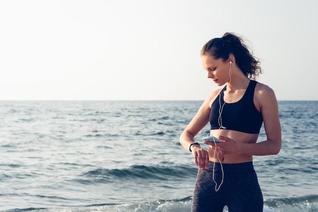 Fille sur la plage tenant un téléphone portable avec un casque à la main et vérifie les données avec smartwatches Photo Premium