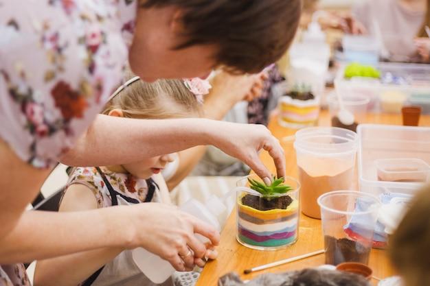 La fille plante une forme de verre, plante des fleurs, terarium de verre Photo Premium