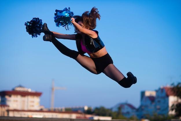 Fille de pom-pom girl à pompons exécute un élément acrobatique à l'extérieur sur le toit Photo Premium
