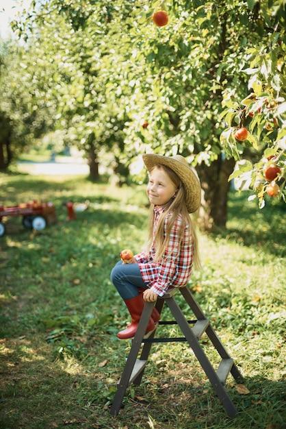 Fille avec pomme dans le verger de pommiers. belle fille mange des pommes biologiques dans le verger. Photo Premium