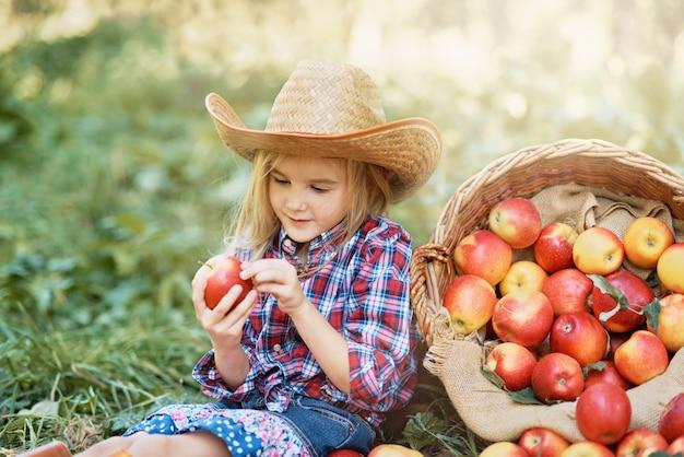 Fille avec pomme dans le verger de pommiers. Photo Premium