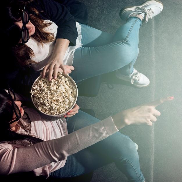 Fille avec pop-corn au cinéma Photo gratuit