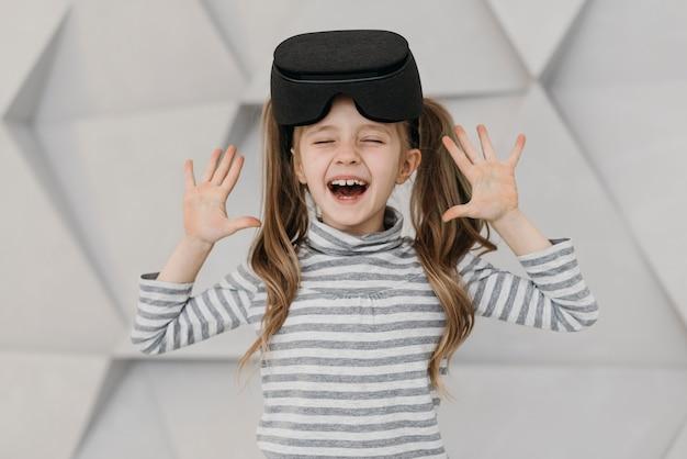 Fille Portant Un Casque De Réalité Virtuelle Et être Heureux Photo gratuit