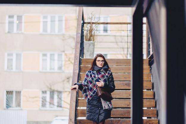 Une fille portant des lunettes en hiver porte des escaliers en bois Photo Premium