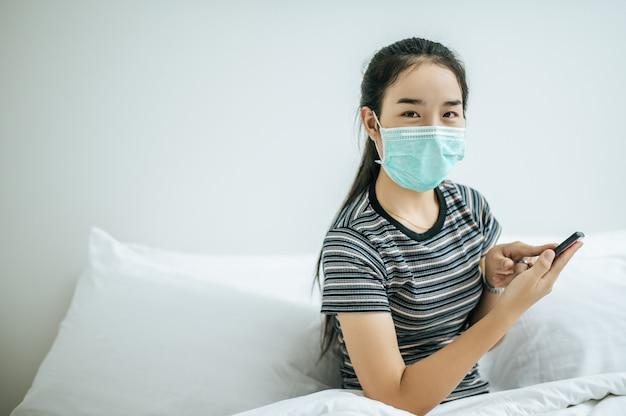 Une Fille Portant Un Masque Et Une Chemise Rayée Jouant Un Smartphone. Photo gratuit