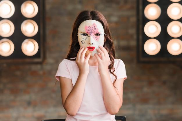 Fille portant un masque debout contre la lumière de la scène Photo gratuit