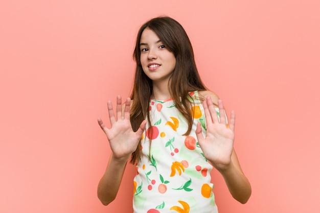 Une fille porte des vêtements d'été contre un mur rouge et rejette quelqu'un qui montre un geste de dégoût. Photo Premium