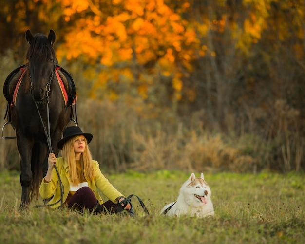 Fille posant avec un cheval et un chien Photo gratuit