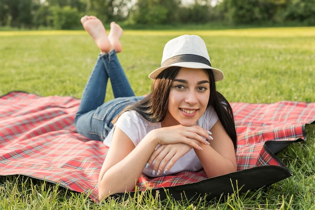 Fille posant sur une couverture de pique-nique Photo gratuit