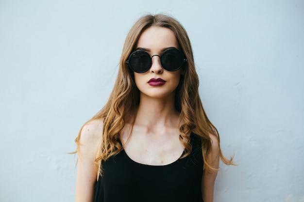 Fille posant avec des lunettes de soleil Photo gratuit