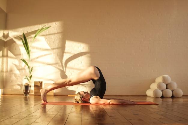 Fille pratiquant des positions de pilates dans un magnifique studio Photo Premium