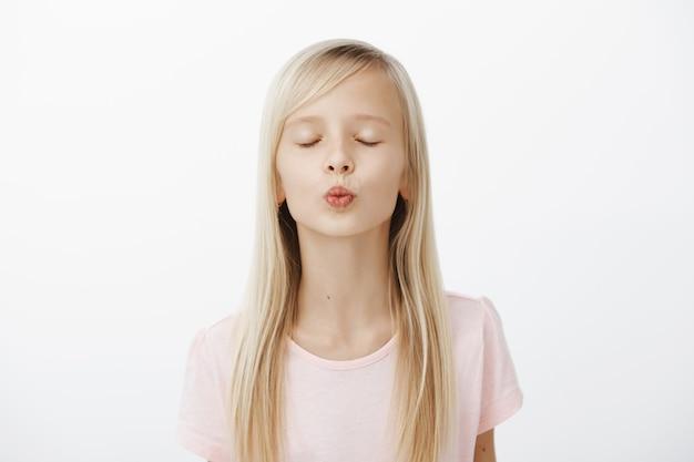 Fille Pratiquant Près Du Miroir Comment Embrasser. Portrait De Jolie Jeune Fille à La Mode Aux Cheveux Blonds, Plier Les Lèvres Et Fermer Les Yeux En Attendant Un Baiser Photo gratuit