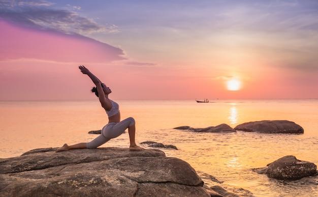 Fille Pratiquant Le Yoga Sur Un Rocher Photo Premium