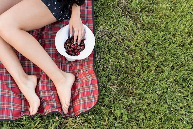 Fille prenant des cerises assis sur une couverture de pique-nique Photo gratuit