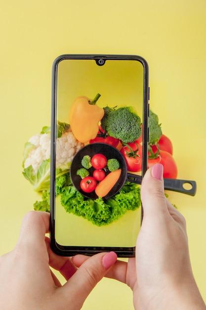 Fille Prenant Une Photo De Nourriture Végétarienne Sur Table Avec Son Smartphone. Concept Végétalien Et Sain. Photo Premium