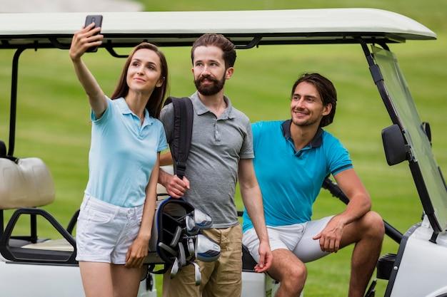 Fille prenant selfie avec des amis sur le terrain de golf Photo gratuit