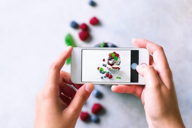 La fille prend des photos du petit-déjeuner, du pudding au chia avec des baies sur son téléphone portable. Photo Premium