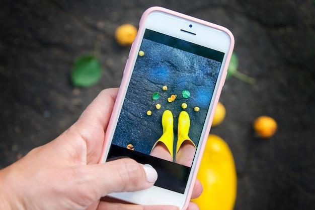 Une fille prend des photos de ses jambes en bottes jaunes au téléphone. un concept de pluie d'été. Photo Premium