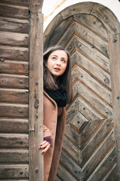 Fille près de la vieille porte en bois Photo Premium