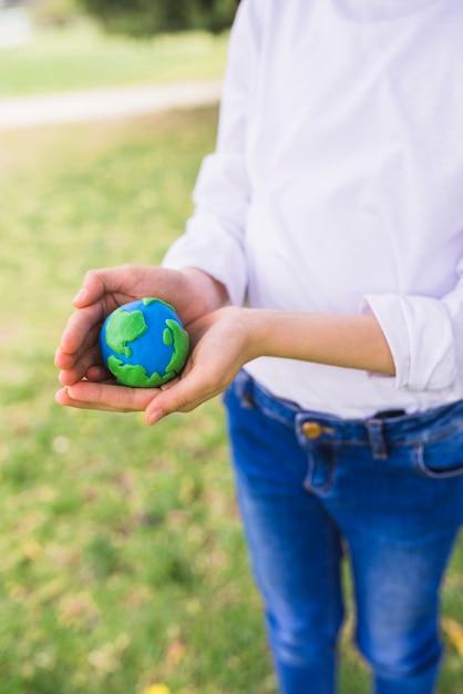 Fille protégeant le globe d'argile avec ses mains Photo gratuit